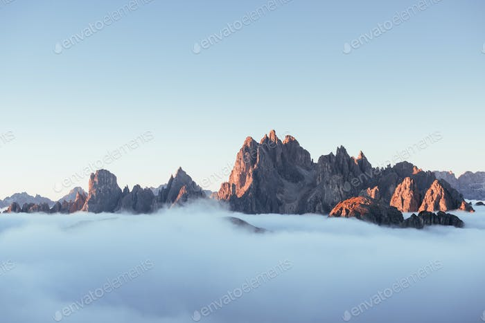 The peaks of the mountains stifle from a going thick fog. Unbelievable photo takes