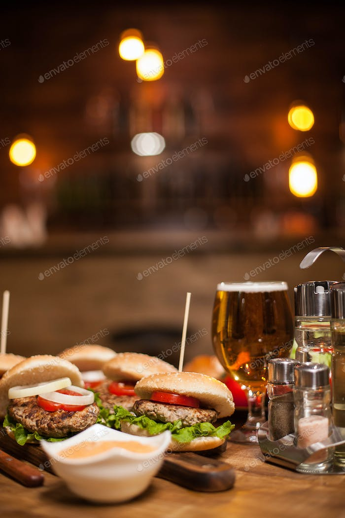 Close-up of delicious fresh home made burgers with lettuce, cheese and tomato with white sauce on a