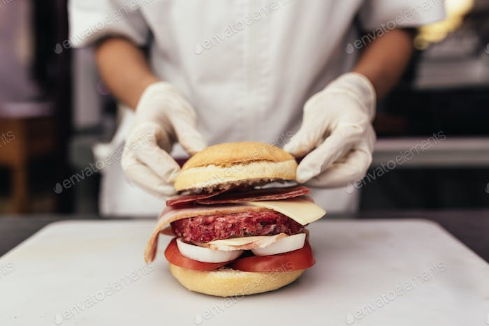 Chef cooking and decorated Hamburger.