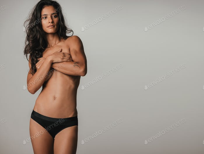 Woman covering breasts over gray background