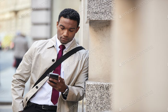 Young black businessman leaning on a wall in the street in London using smartphone, selective focus