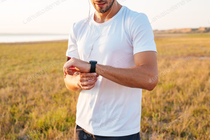 Sports man looking at his smartwatch with earphones