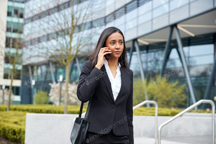 Businesswoman Commuting To Work Talking On Mobile Phone Outside Modern Office Building
