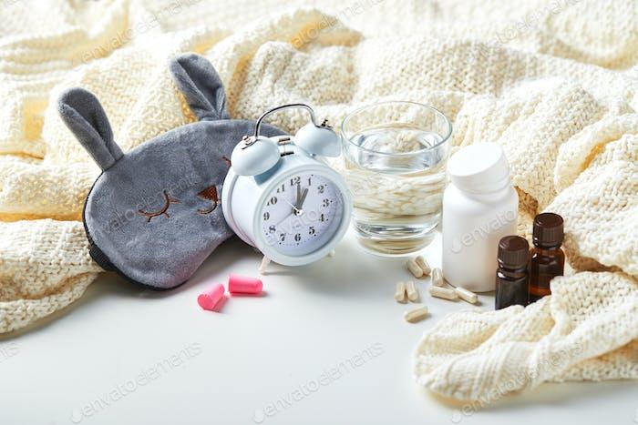 Sleeping mask, alarm clock, earplugs and pills. Healthy night sleep creative concept
