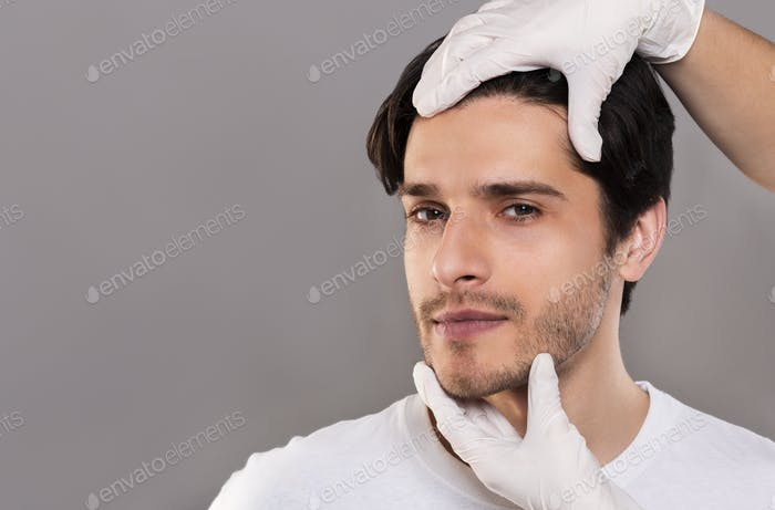Plastic surgeon examining male patient face, empty space