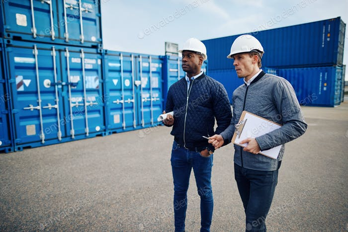 Two engineers discussing logistics in a large shipping yard