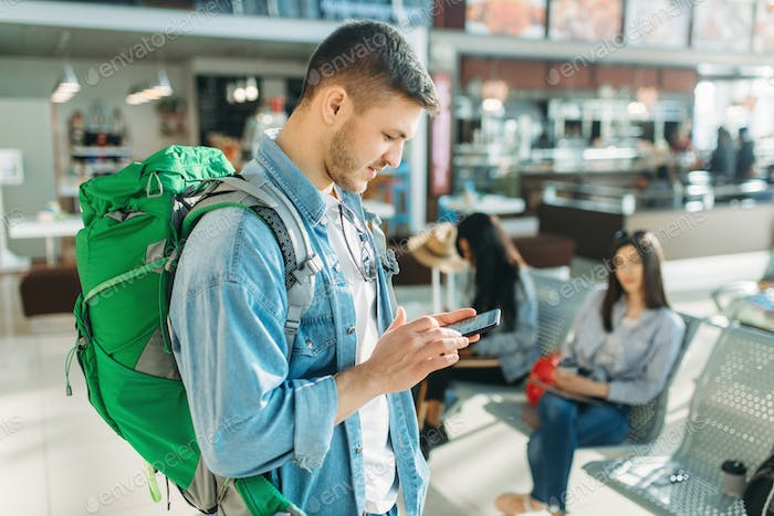 Male tourist with backpack holds phone in airport