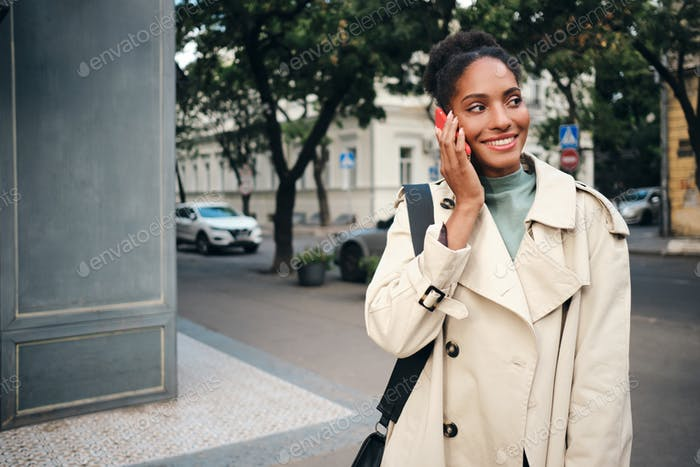 Beautiful African American girl in stylish trench coat happily talking on cellphone on city street