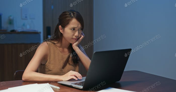 Woman feeling tired on look at the laptop computer at home in the evening