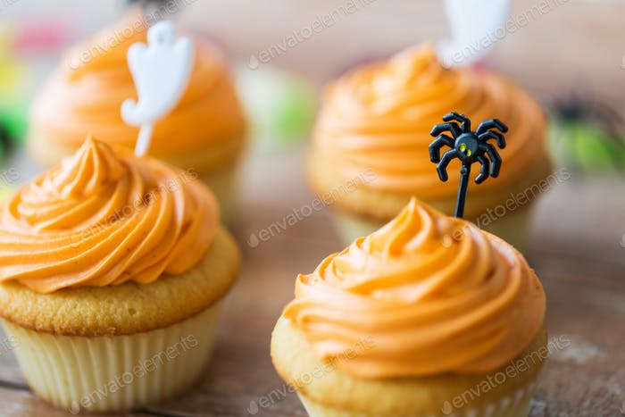 cupcakes with halloween decorations on table