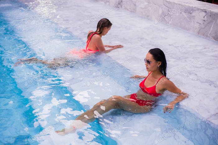 two young beautiful women in jacuzzi of resort