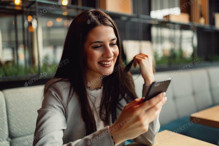 Pretty businesswoman using smart phone.