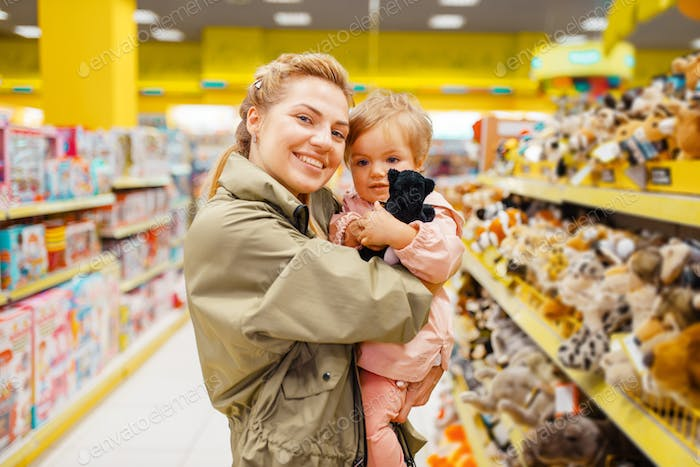 Mother with girl choosing plush dog in kids store