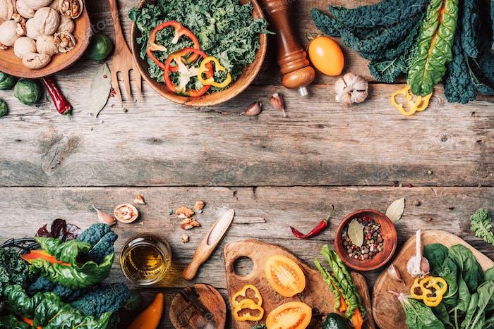 Frischer Grünkohl, Spinat, Avocado, Nüsse, Pfeffer, Gemüse, Salz, Gewürze, Öl auf rustikalem Holz