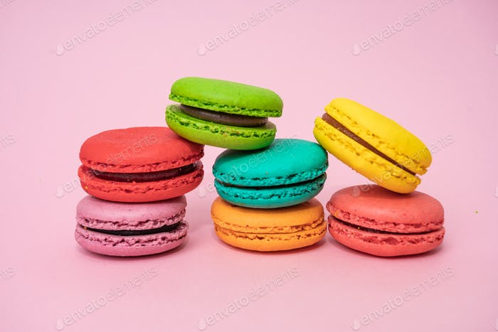 Multicolored macaroons on pink background. Sweet and colourful french macaroons