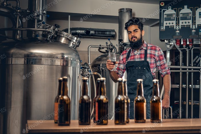 Indianr male manufacturer presenting craft beer in the microbrewery.