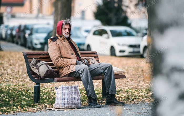 Homeless beggar man with a bag sitting on bench outdoors in city. Copy space.