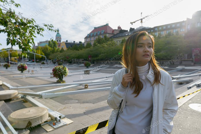 Young beautiful Asian tourist woman thinking in empty town square outdoors