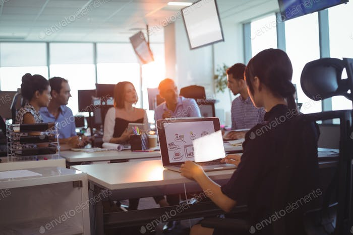 Businesswoman working on laptop while colleagues discussing at desk