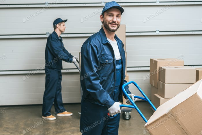 two movers in uniform transporting cardboard boxes with hand trucks in warehouse