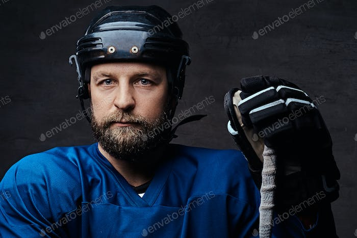 Middle-aged bearded hockey player wearing full sports equipment with a hockey stick