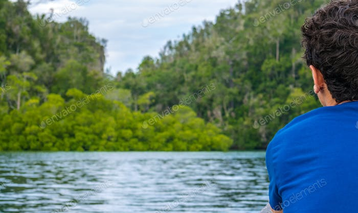 Traveler looking into Mangrove Jungle near Warikaf Homestay, Kabui Bay and Passage. Gam Island, West