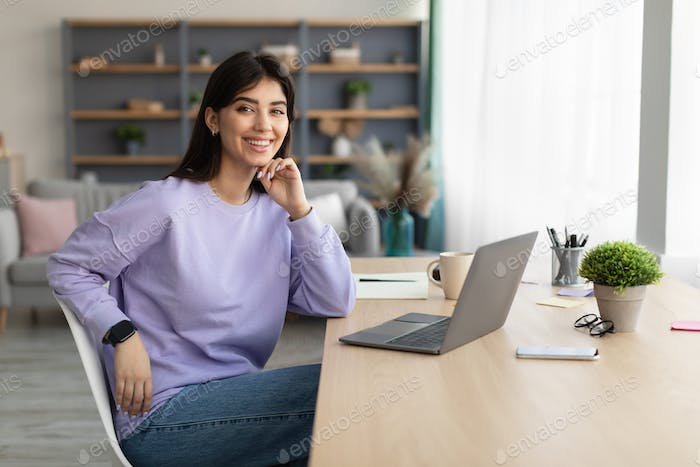 Portrait of smiling young woman sitting at desk