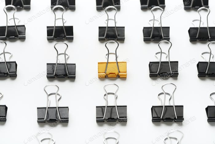 Golden binder clip standing between black ones