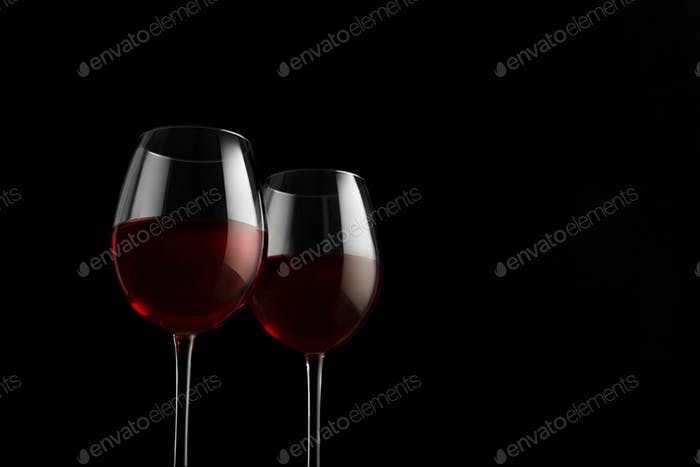 Two red wine glasses on a black background
