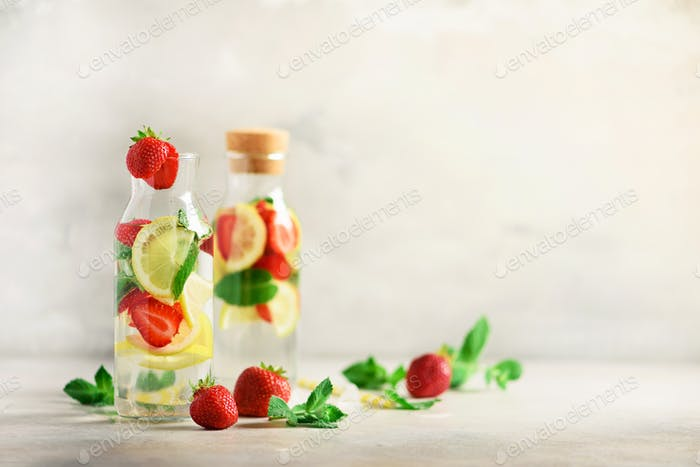 Citrus and strawberry lemonade with mint, lemon on grey background. Detox drink. Summer fruit