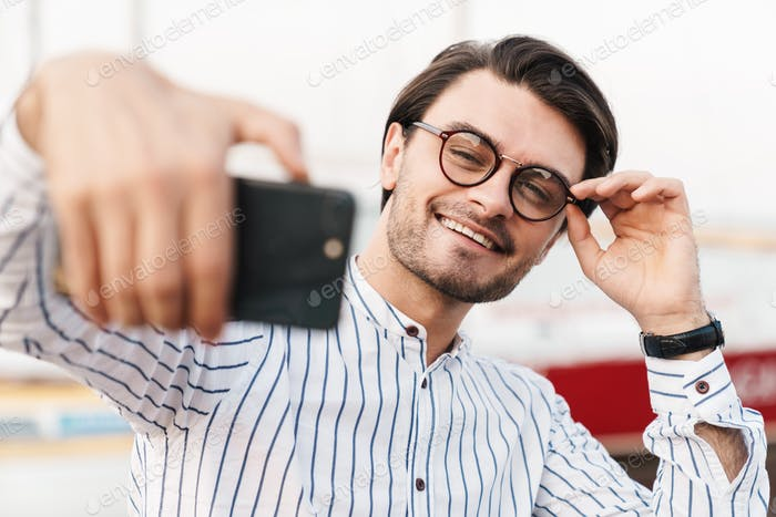 Photo of cheerful young man taking selfie photo on smartphone and smiling while walking on pier