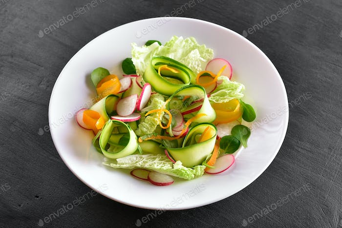 Vegetable salad on dark stone background