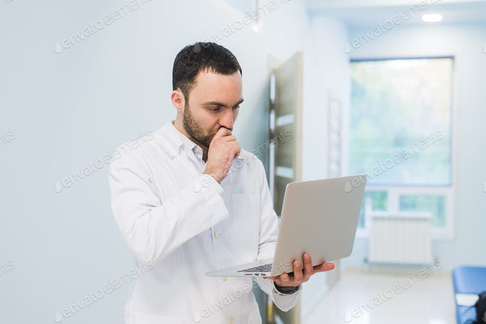 Minded successful doctor standing at his office and using laptop for his work