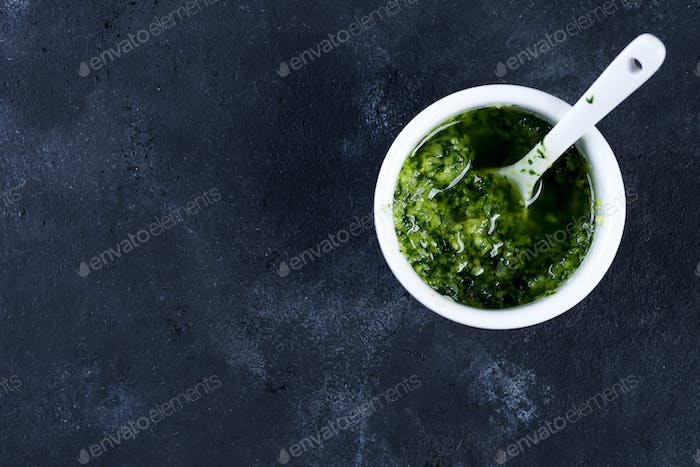 Homemade basil pesto with parsley in bowl. Top view. Vegan healthy food