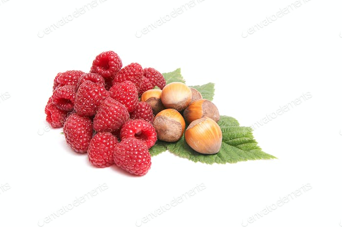 Juicy raspberries and nuts on a white.