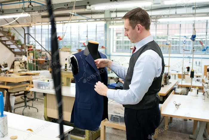 Tailor working over mannequin with jacket