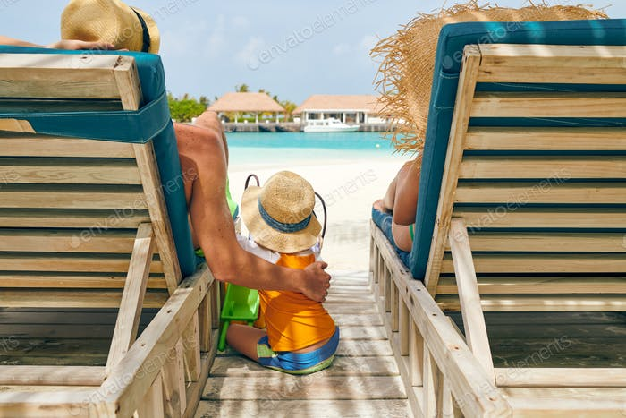 Family at beach on wooden sun bed loungers