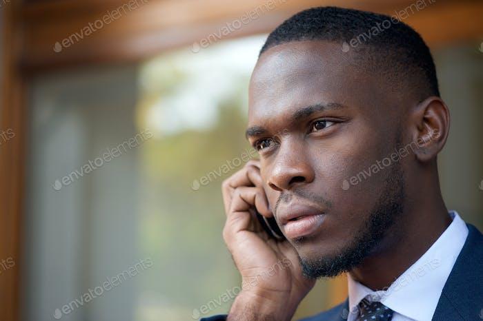 Афро-американский бизнесмен разговаривает по мобильному телефону