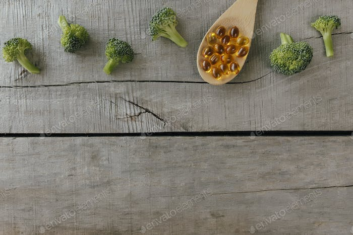 Omega 3 pills, broccoli, wooden spoon and background. Natural medicine concept
