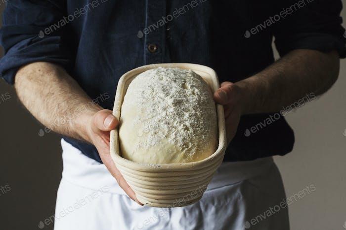 Nahaufnahme eines Bäckers, der einen frisch gebackenen Laib Weißbrot in einem Rattan-Proofing-Korb hält.