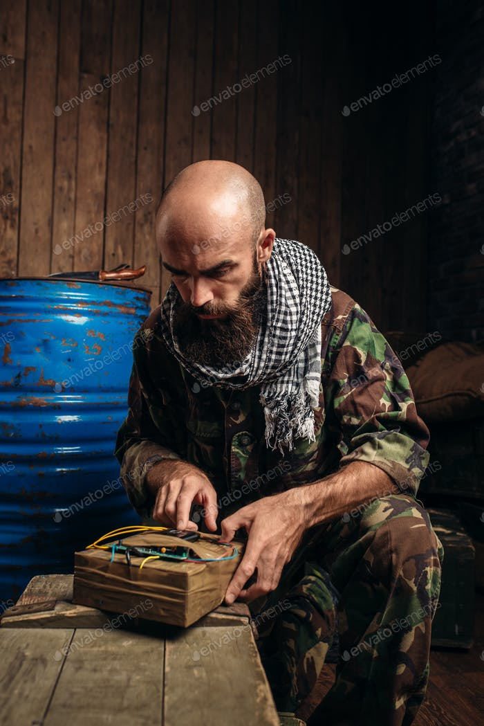 Bearded terrorist in uniform cooking a bomb