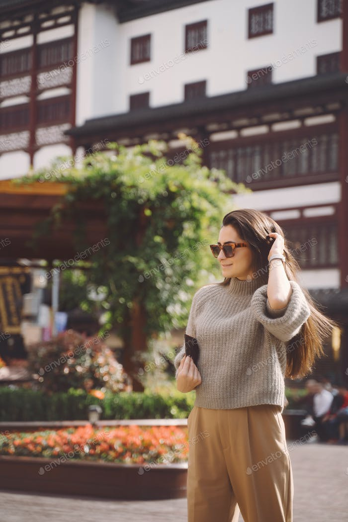 brunette girl exploring a local square in Shanghai China