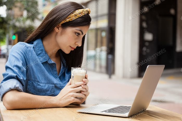 Woman using laptop computer while holding cold coffee