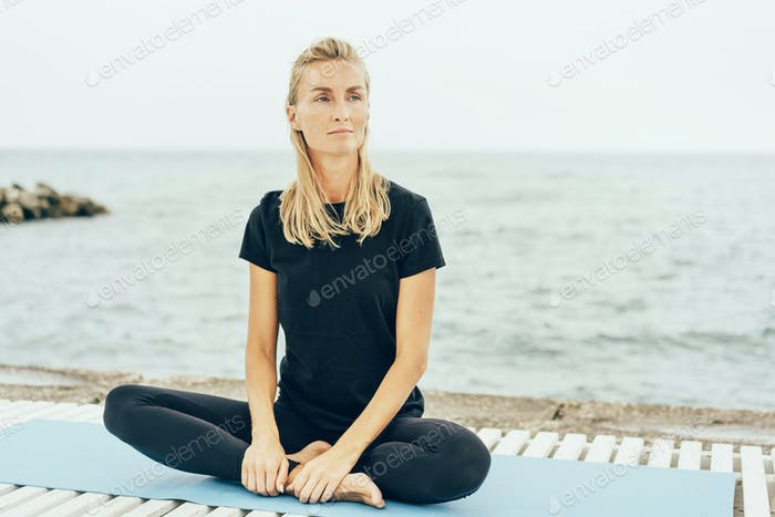 A young slender woman sits in a lotus position after a basic sports training on the bay.