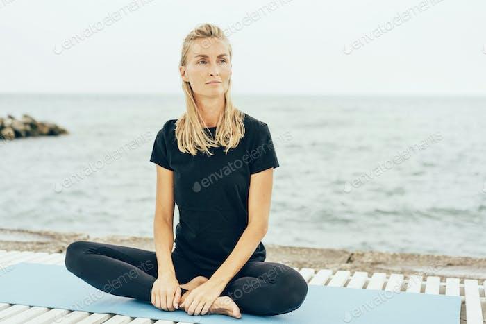 Eine junge schlanke Frau sitzt nach einem grundlegenden Sporttraining an der Bucht in Lotusposition.