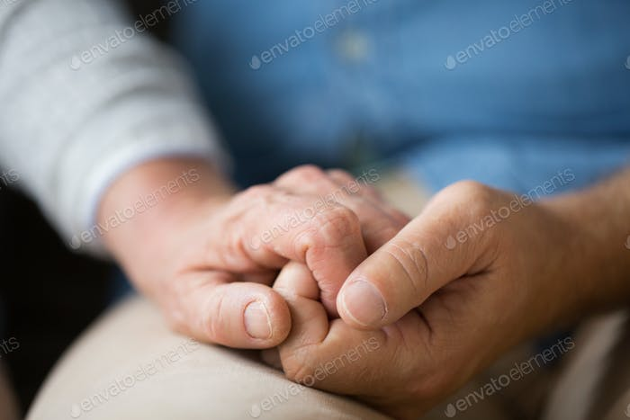 close up of senior couple holding hands