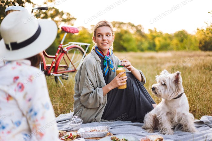 Beautiful girl holding smoothie bottle in hand while dreamily lo