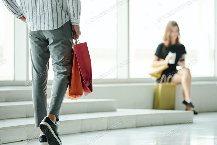 Man approaching to girlfriend after shopping