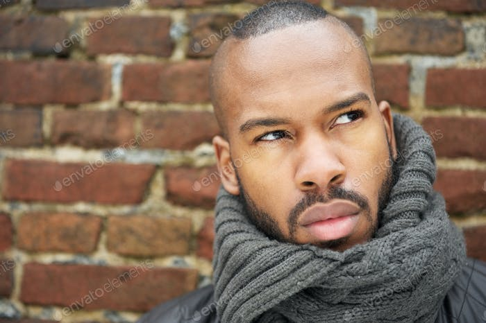 Young african american man with gray scarf looking up