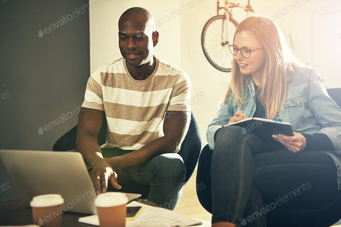 Smiling colleagues discussing work together in a stylish modern office